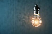 Glowing Light Bulb On Gray Wal...