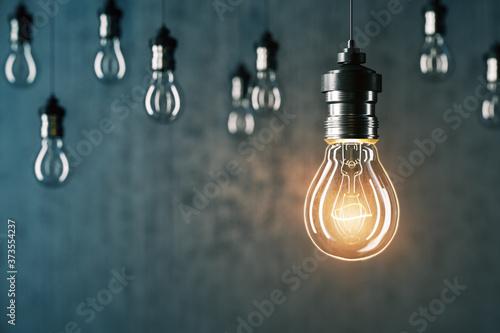 Obraz Glowing light bulb and many light bulbs - fototapety do salonu