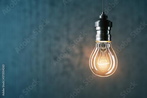 Glowing light bulb on gray wall background. Fototapet
