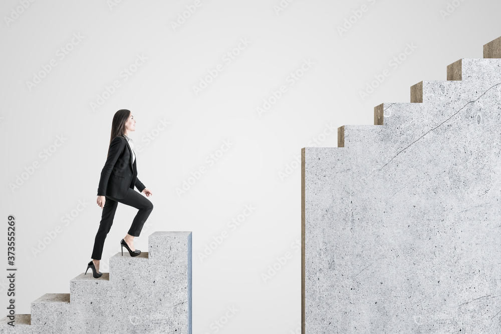 Fototapeta Businesswoman walking on intermittent concrete staircase