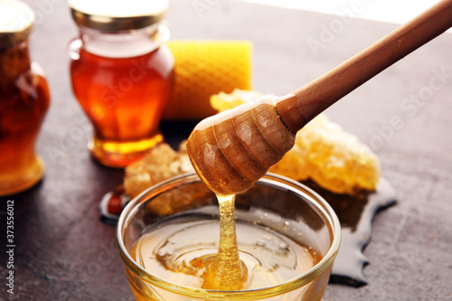 Photographie Honey in jar with honey dipper on vintage rustic background