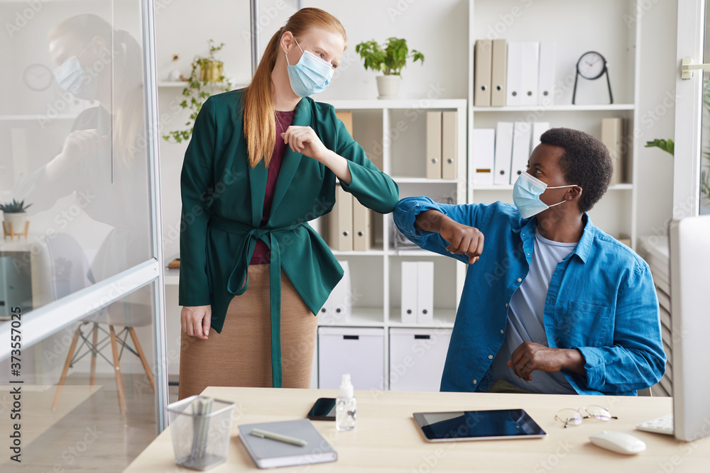 Fototapeta Portrait of young businesswoman wearing mask bumping elbows with African-American man as contactless greeting in post pandemic office, copy space