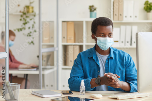Canvastavla Portrait of young African-American man wearing face mask and sanitizing hands wh