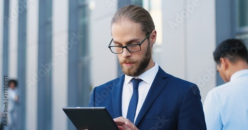 Handsome Caucasian young businessman in glasses, suit and tie using tablet device at street Canvas Print