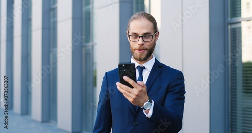 Foto Caucasian handsome young businessman in glasses, suit and tie standing at street at business center and talking via videochat on smartphone