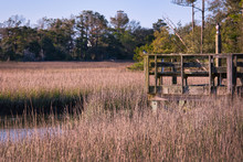An Old Wooden Dock By A Creek In A Salt Marsh Near Pawleys Island, South Carolina, USA, In The Winter.