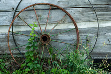 Old Rusty Wheel Leaning On Log...