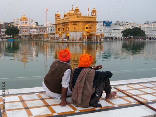 Fotografie, Obraz two sikh men sitting beside golden temple' s pool in amritsar