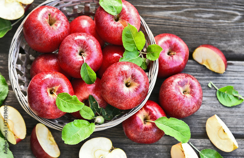 A lot of fresh Royal Red Gala apples with green leaf  in basket on wooden background Poster Mural XXL