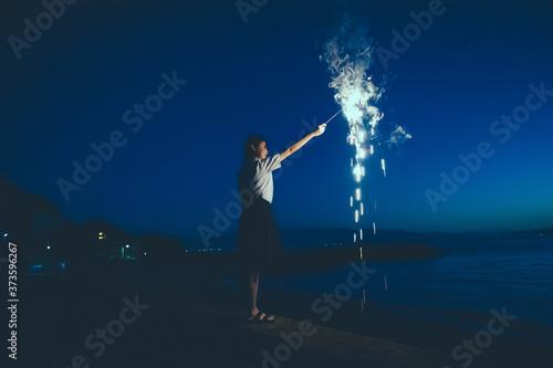 Photo 夜の海で花火をする女子高生