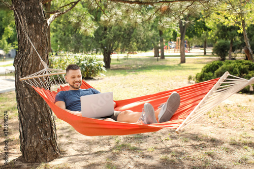 Valokuva Handsome man with laptop relaxing in hammock outdoors