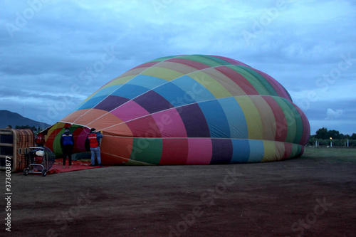 Photo process of inflation and preparation of hot air balloon at sunrise for flight in