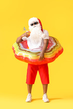 African-American Santa Claus With Inflatable Ring On Color Background