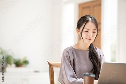 Leinwand Poster パソコンを使いながらZoomなどでリモートワークのミーティングの準備をする若い日本人女性左側にコピースペースあり