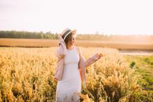 A Girl In A Straw Hat In A Fie...