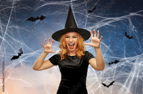 Fotografie, Obraz holiday, theme party and black magic concept - scary woman in halloween costume