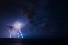 Thunderstorm Over The Sea With Dark Clouds And Multiple Lightning Bolts In The Lower Left Corner
