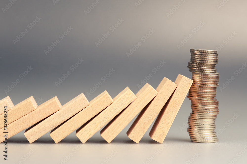 Fototapeta Money coins heap still balance and stop the falling domino, financial stability concept