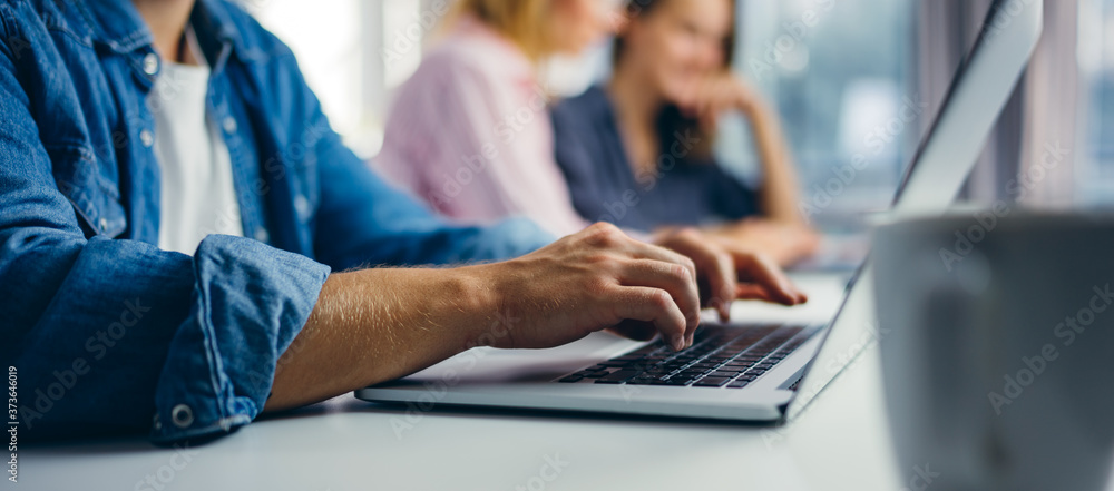 Young man typing on laptop. Businessman at sunny office. Freelancer at work. Blogger or journalist writing new article - obrazy, fototapety, plakaty
