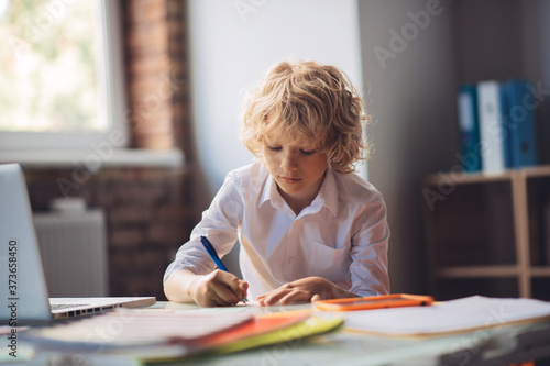 Fototapeta Cute blonde boy sitting at the table and writing
