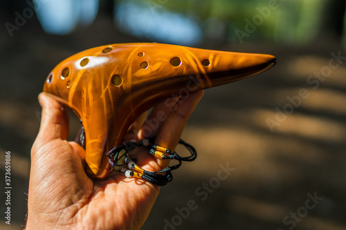 Caucasian man's hand holding a traditional brown ceramic ocarina in natural light in the middle of nature Fototapete
