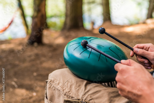 Stampa su Tela Close-up with the hands of a Caucasian musician holding drum sticks and playing a modern handpan steel tongue drum percussion musical instrument in the middle of nature