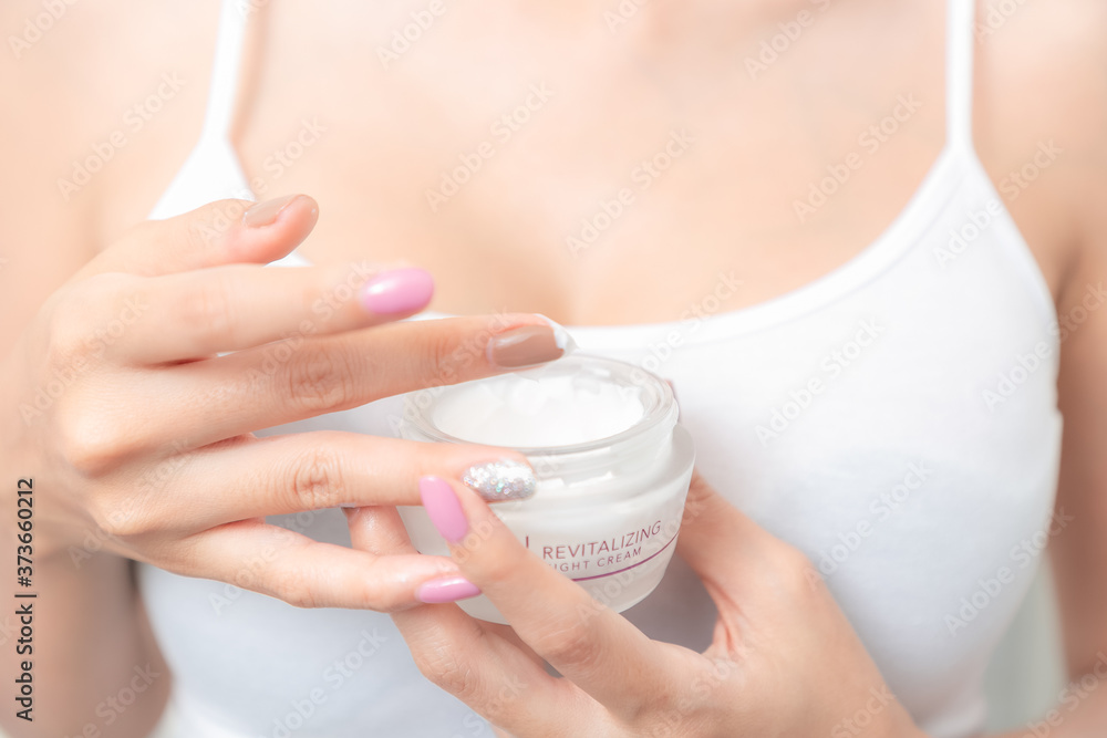 Fototapeta A woman holds a moisturizer in her hand and her skin and wrinkle from impurities.