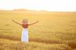 Mujer en el campo con los brazos abiertos hacia el sol del atardecer