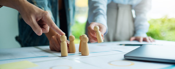 A group of business team brainstorming and planning strategy together with.wooden people in a meeting