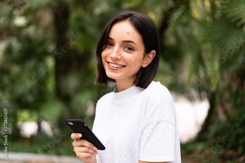 Fototapeta Young caucasian woman using a phone at outdoors obraz