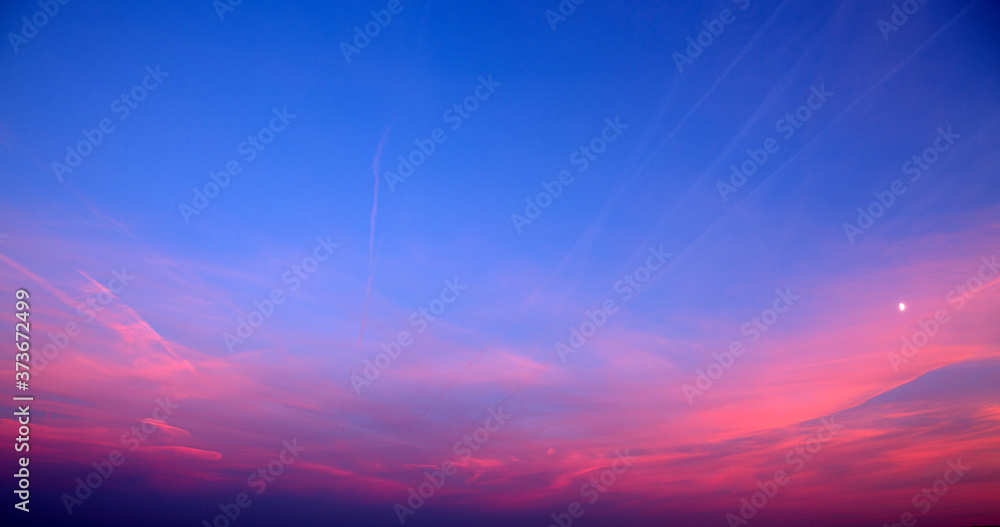 Fototapeta Sunset with pink clouds, light rays and other atmospheric effect.