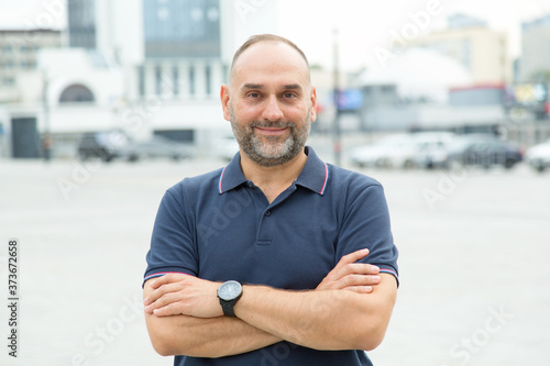Fototapeta Bearded smiling middle-aged man on the background of a city street