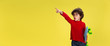 Pointing. Portrait of pretty young curly boy in red wear on yellow studio background. Childhood, expression, education, fun concept. Preschooler with bright facial expression and sincere emotions