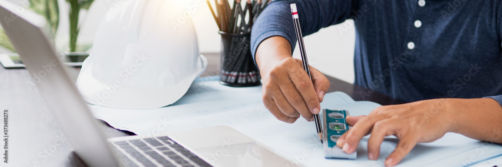 Fototapeta Architect working in office with blueprints,engineer thinking and planning inspection in workplace for architectural plan,sketching a construction project,Business construction concept.