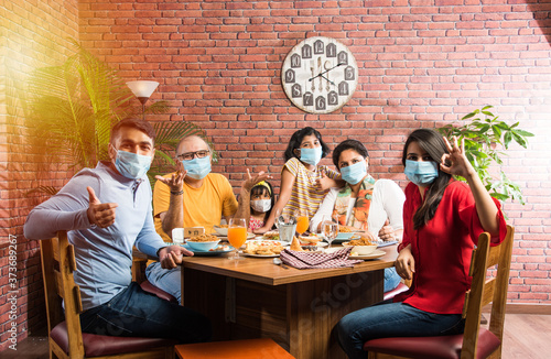 Obraz Indian family wears face mask while eating food in restaurant after corona pandemic unlock - concept showing new normal lifestyle in India - fototapety do salonu
