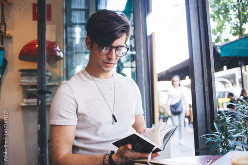 Fotografía Concentred young man searching information in notebook
