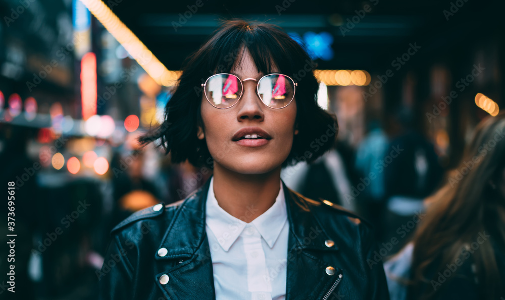 Fototapeta Caucasian woman in optical spectacles with neon reflection of lights standing at urbanity during travel vacations for visiting New York, attractive hipster girl in trendy apparel going out