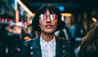 Caucasian woman in optical spectacles with neon reflection of lights standing at urbanity during travel vacations for visiting New York, attractive hipster girl in trendy apparel going out