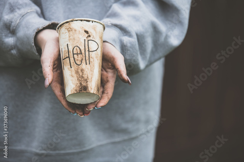 person with dirty hands holding a dirty paper cup with the word help Fototapeta