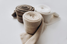 Three Rolls Of Cashmere In Different Pastel Colors With On White Background. Selective Focus. Close Up View. Blurred Background