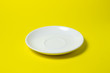 Leinwanddruck Bild - White saucer on a yellow background. An empty pink saucer lies on a yellow surface