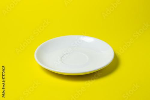 Obraz na płótnie White saucer on a yellow background