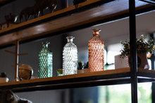 A Group Of Classic Glasses Flower Vases On The Wooden Shelf, Using For Interior Decoration. Selective Focus On The Right One (orange Color Object).