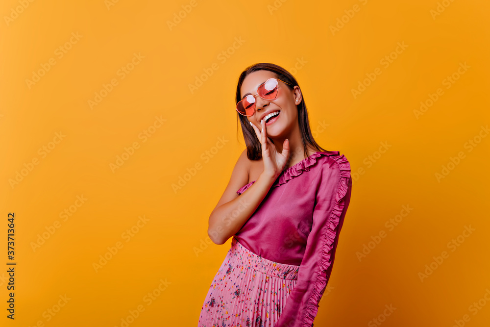 Fototapeta �lm woman in pink top with frill poses, showing joy. Photo of model with nude makeup in cozy atmosphere
