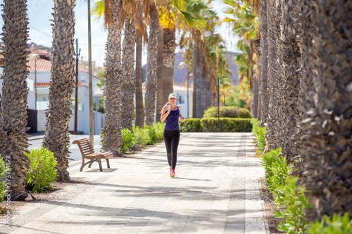 Fotografie, Obraz Smiling girl running on the street in tropical city