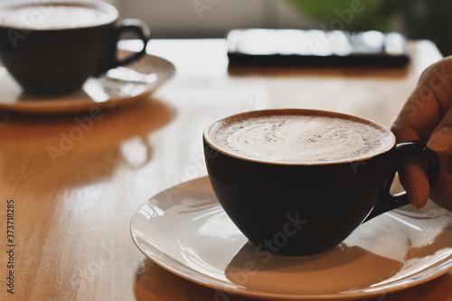 Fotografie, Obraz Hot coffee in a black cup on wooden table.