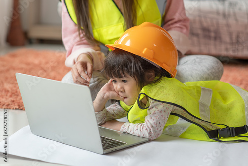 Little Asian girl engineer in yellow helmet using laptop with her mother, educat Tapéta, Fotótapéta