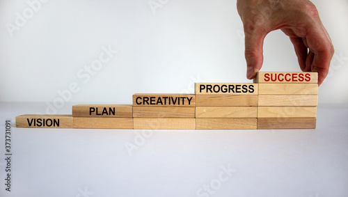 Fototapety, obrazy: Business concept growth success process. Male hand. Wood blocks stacking as step stair on white background, copy space. Words 'vision, plan, creativity, progress, success'.