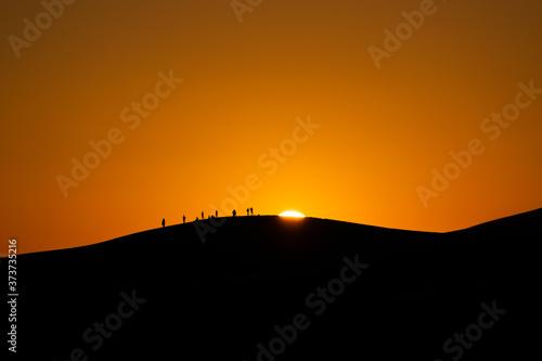 panorama dell'alba nel deserto marocchino di merzouga, con persone sullo sfondo Wallpaper Mural