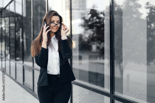 Fotografiet Successful smiling businesswoman or entrepreneur talking to the phone standing in front of his office